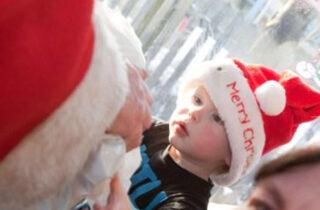 Santa Trains Little Boy Receiving Gift